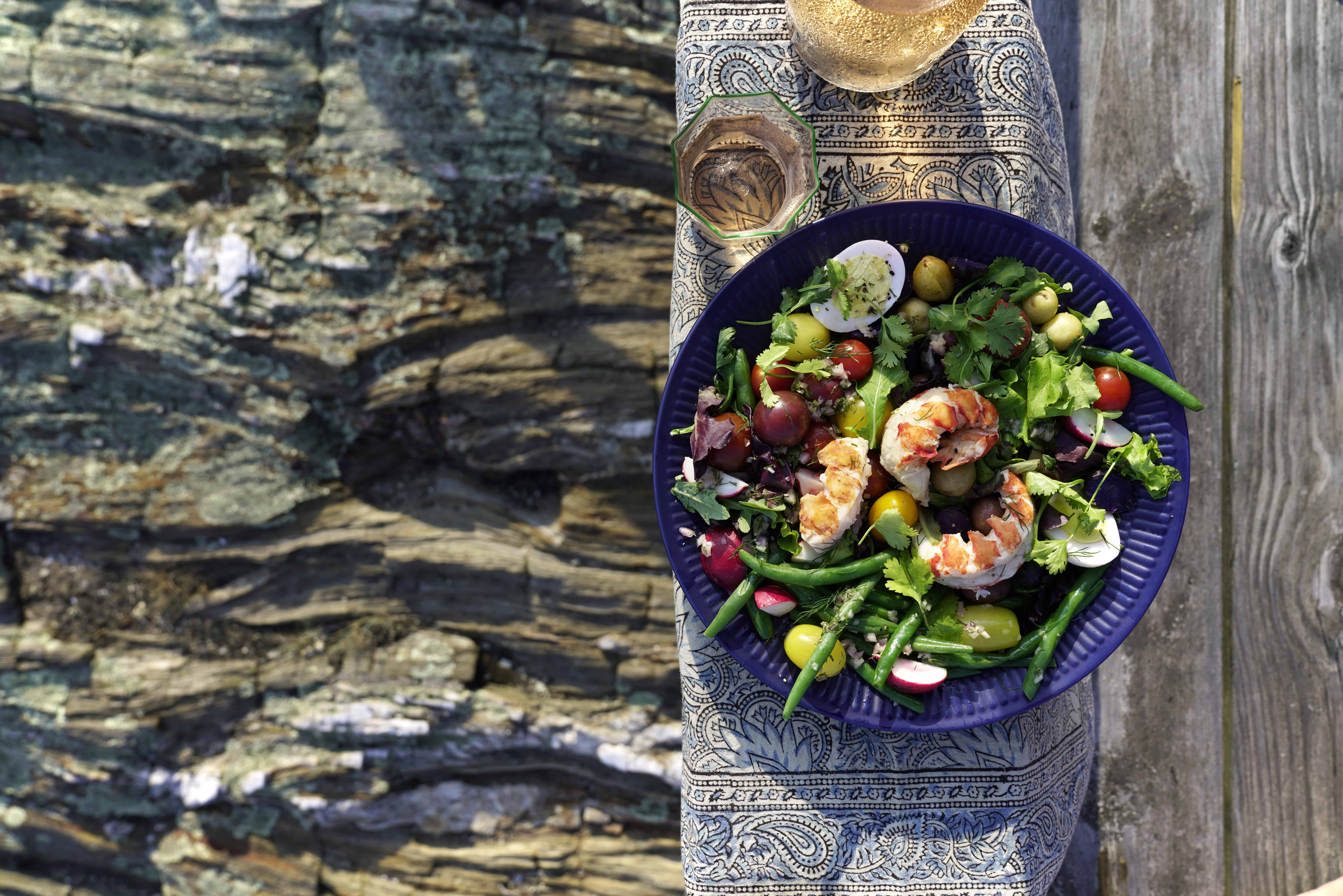 colorful farmers market salad with whole lobster tails on a wooden deck above the rocky coast
