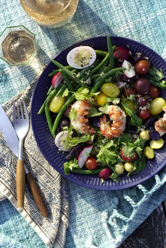 Colorful farmers market produce with whole lobster tails and a glass of rose